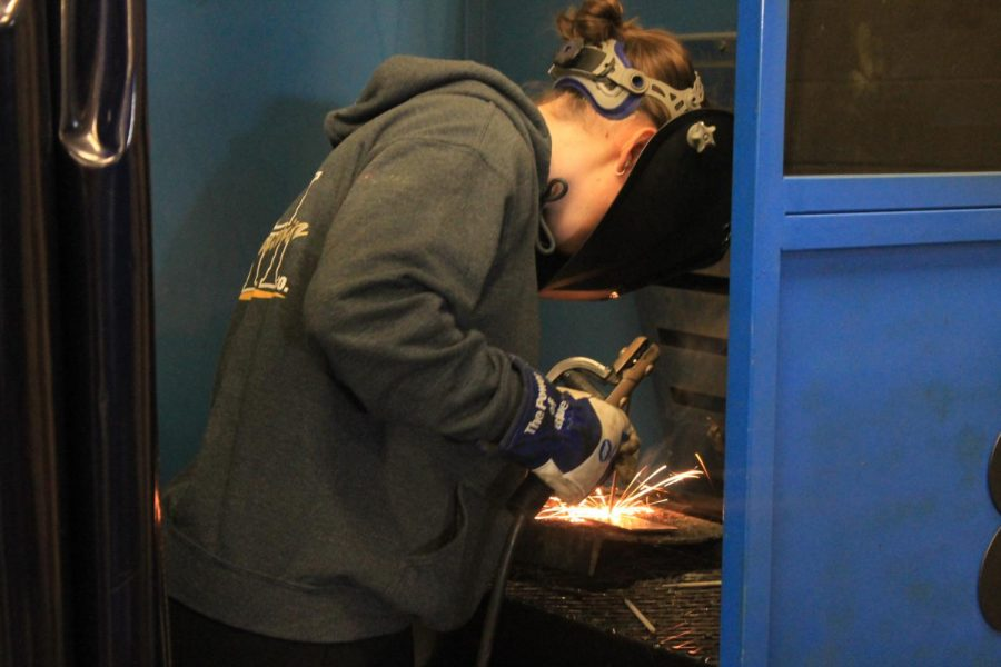 "Working Hard: During third hour in Welding I, Cadance Rohrer (22) is found in one of the shop classes' many welding booths working on one of her projects. ""To me, welding is very easy-going as long as you handle the equipment right,"" Rohrer said. ""That is one of the reasons why we wear masks; people can blind themselves from the light produced by the flames. Along with that, we have to wear gloves so that we don't burn ourselves while holding hot materials."" Rohrer is currently enrolled in Welding I and is expected to take Welding II either next semester or next year."