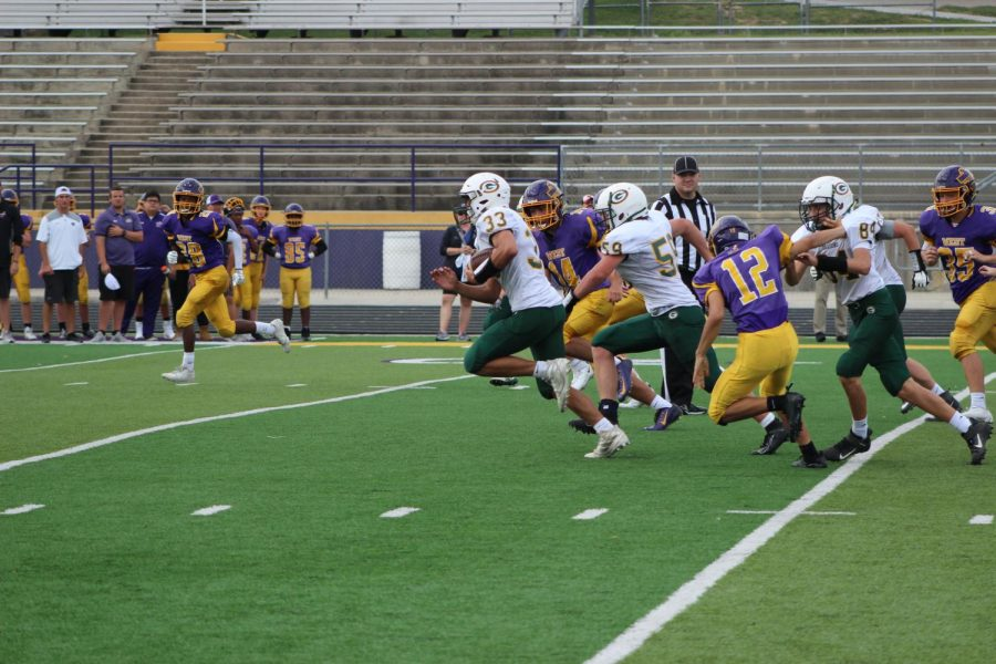 Sophomore Mick Huber taking the ball for a touchdown while junior Jacob Taylor blocks for him at Bellevue West High School.