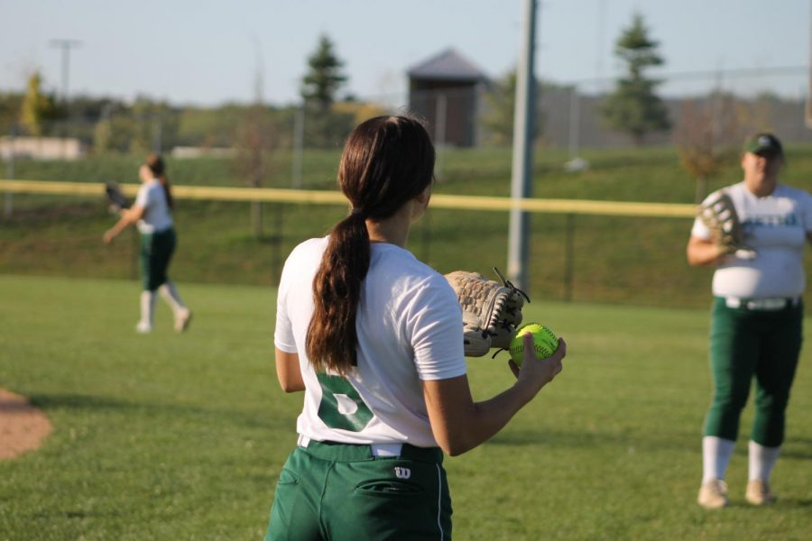 Warming up her arm is sophomore Molly Hahn who is playing catch with her teammate.