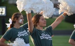 The cheer finishes and Junior Lily Brown raises her arms as she spirits to the crowd.