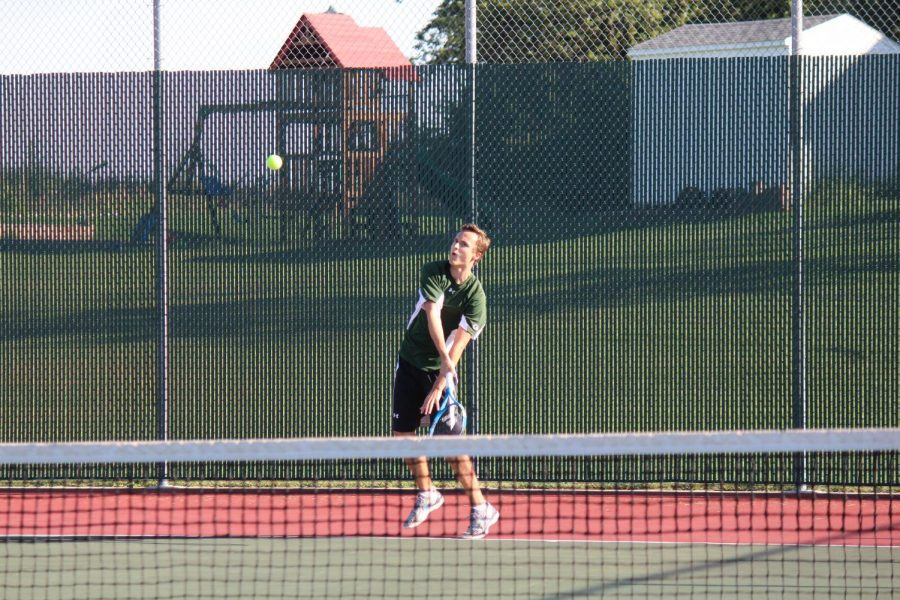 In the game against Burke High School, Sophomore Austin Roespies is getting ready to forehand the ball.