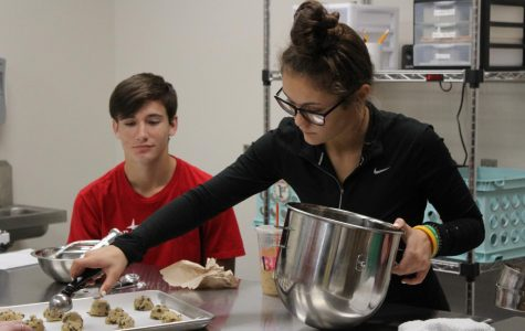 Seniors Carlyn Briganti and Samuel Strong scoop out balls of cookie dough during the cookie contest.