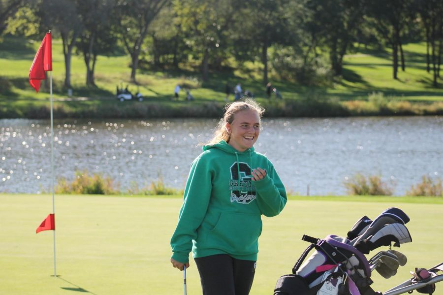 During practice, freshman Shaylee Sockel smiles as she finishes the hole.