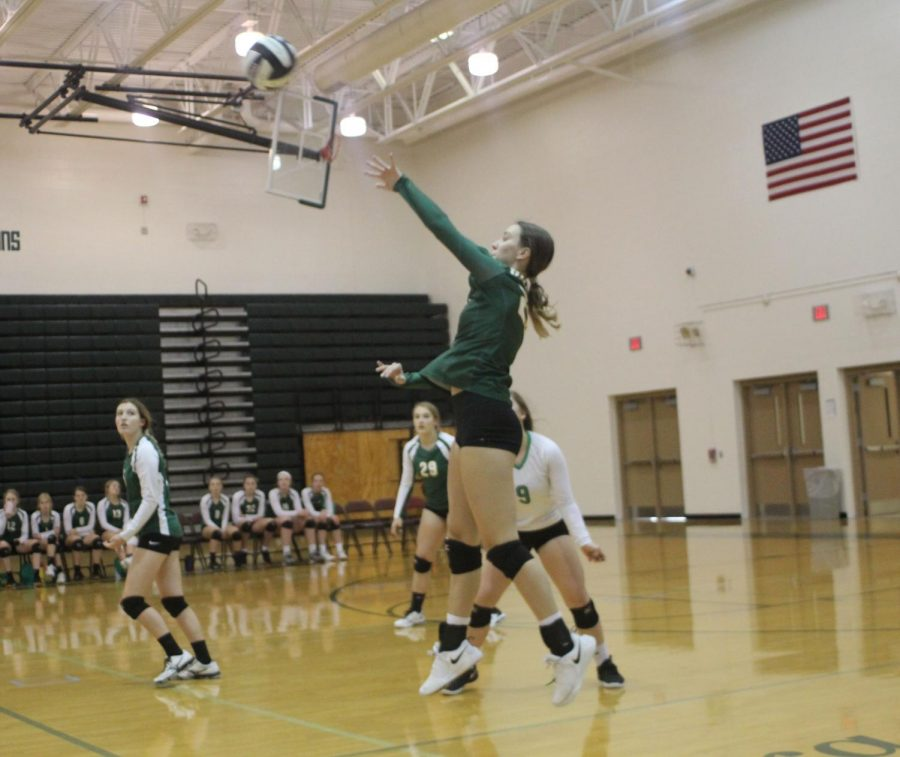 Katelynn Cogswell jumps as she hits the ball over the net.