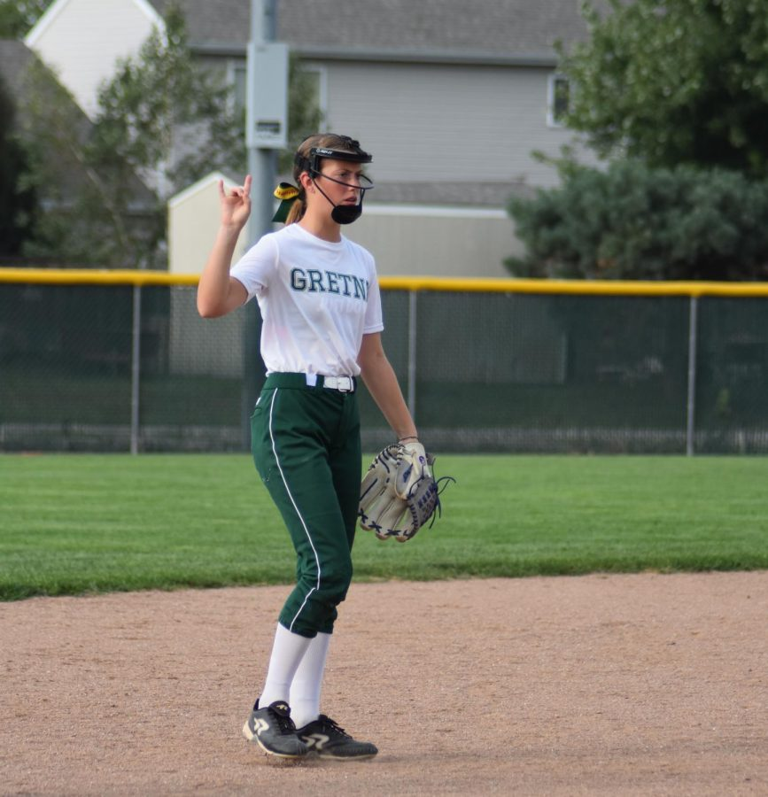The shortstop, freshman Shaylynn Campbell, showing the team that there are two outs.