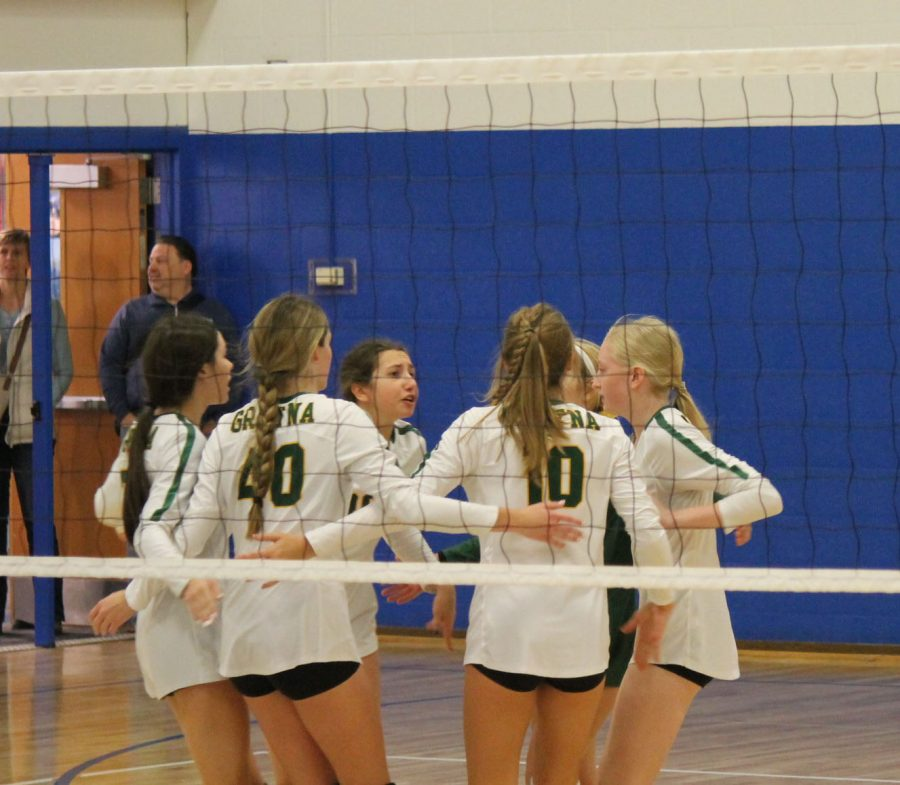 Freshmen Volleyball team members circle up before the next serve.