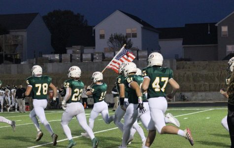 Senior Coby Speer running the American Flag before the game against Fremont.