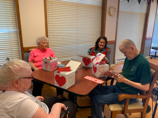 Distribution Day: Gathered around a table, four elders from the Gretna Family Community Center are reading their Valentine Day cards. The cards were made throughout the week of Feb. 13 and were created by a combination of students from grades K-12. Each elder received about five cards in their boxes.