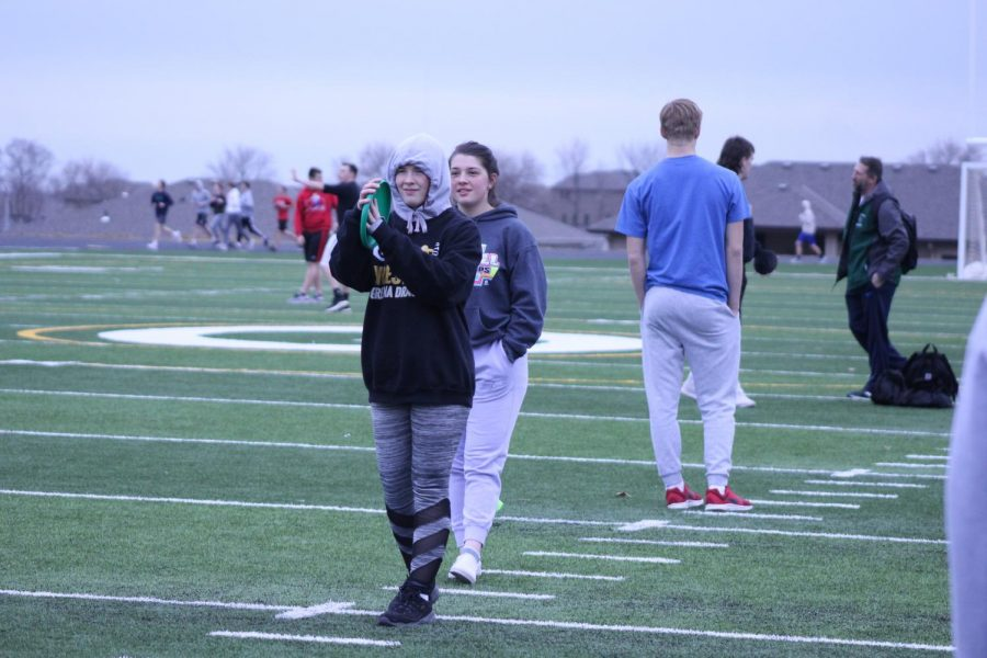 Stephanie Kittleson (22) and Kristen Keith (22) are practicing their discus shots during one of their after school track and field practices.