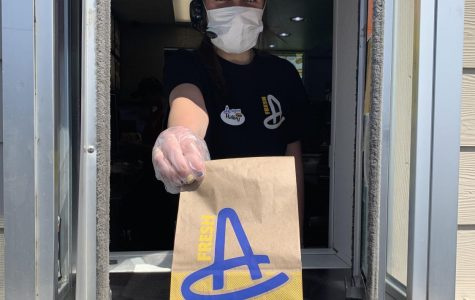 Staying Protected: When interacting with customers, Hailey Wojtas (22) keeps herself protected by wearing gloves and a mask.