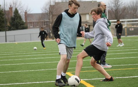 Joey Witt (22) is attempting to steal the ball from Joe Burns (22) during an after school soccer practice.