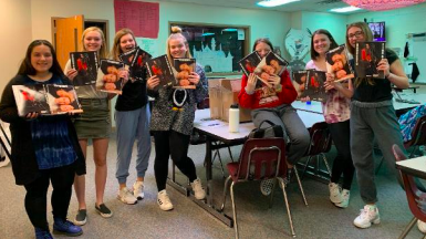 The Vanguard staff holding prints of the magazines they created. Junior Peyton Rewczuk printed them out as a Christmas present to her favorite class.