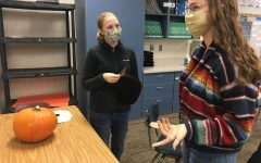 Before painting their Pumpkin, Laynie Aure (22) and Grace Russell (22) discuss ideas.