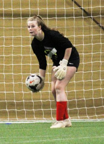 "RED HOT Goalkeeper Kelsey Johnson (21) holds the ball, waiting for her teammates to get open. ""I am most excited for being with everyone and practicing together,"" Johnson said. ""It"