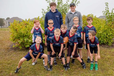 "Team Spirit: The Patriots coached by Colton Munn (21) and Kaden Conrad (21) pose for a silly picture. ""I would highly recommend coaching flag football,"" Conrad said. ""Because it gives us an opportunity to teach kids the game of football while also letting them have fun doing it."" The team finished the season with a record of 3-5."