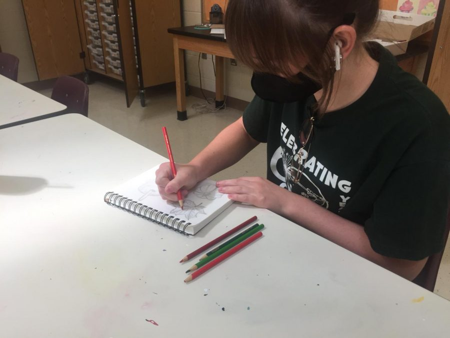 "Creative With Color  Working on the sketchbook project during class, Basic Art student Molly Boker (23) colors leaves that she drew. ""The sketchbooks are for everyone to create their own ideas based off a small prompt like the 3 cartoon/animations and make them scary and ugly sketchbook,"" Boker (23) said. ""My favorite sketchbook so far is drawings about food and the 3 things we're excited about for fall."" Four sketchbook projects have been assigned."