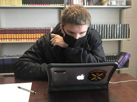 "Keen Eye: Staring intently at his laptop, Ethan Wegner (22) completes the Science quiz. ""I think they did very well at the scrimmage, though it is hard to judge their standing using the scrimmage,"" Mr. Arch said. This is Wegner's first time competing in Academic Decathlon."
