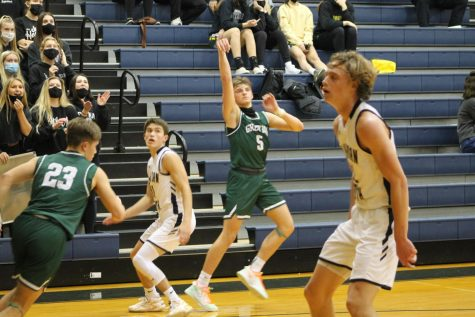 Hold it: Focused on the fundamentals, Blake Rose (21) holds his follow through. The three pointer went down and helped the Dragons retake the lead as the fourth quarter was coming to a close. Rose finished the game shooting 40% from behind the arc.