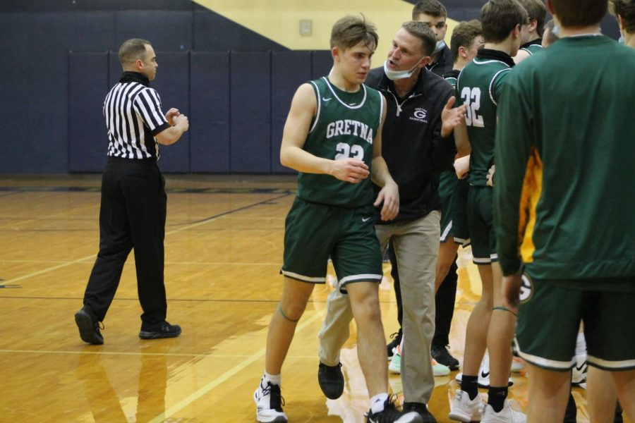Teaching Moment: After calling a timeout, Coach Brad Feeken seeks out starting point guard Landon Pokorski (24).