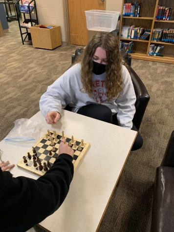 "While playing a round of chess, Samantha Chase (21) analyzes the board for her next move. ""quote from sam"" Chase joined the chess club this year with her friends."