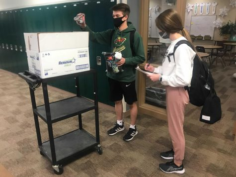 "Staying Organized: At 3:00 p.m. on Friday, Feb. 12, Matthew McKinney (21) and Sarah Turpen (21) walked around the school to collect, count and tally up how many socks were in each first-hour sock box. ""I am the president of the student council, so that is why I was involved in the sock drive,"" Turpen said. ""My job was to advertise to fellow students as well as collect socks."" The donated socks will be evenly distributed between Open Door Mission locations in Lincoln and Omaha."